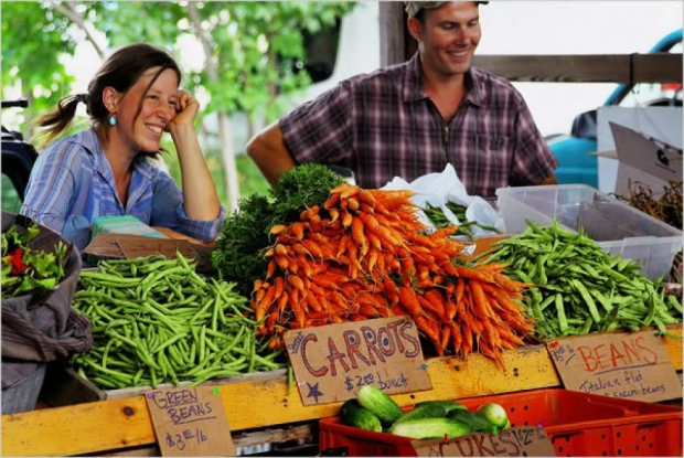 Two vegetable vendors at a market selling green beans, sweet carrots, beans and other vegetables.