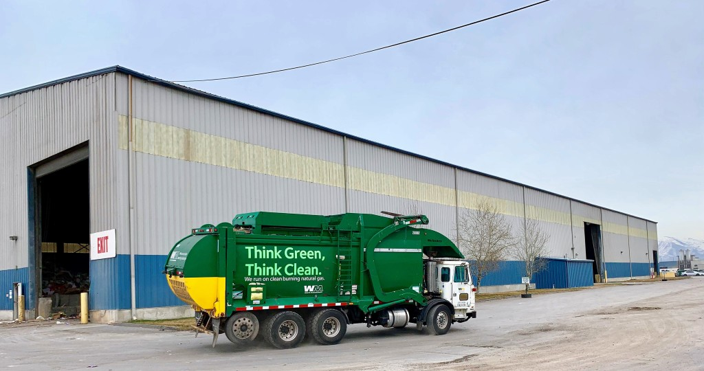 "Photograph of Waste Management collection truck in front of MRF. The truck is green with text that reads ""Think Green, Think Clean."""