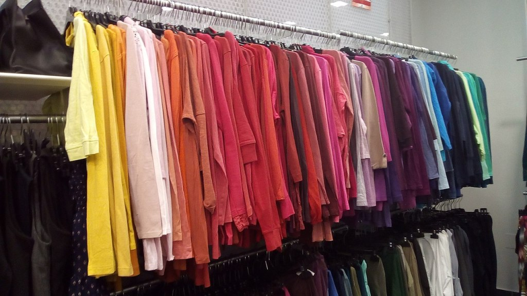 Photo of clothes on sales rack organized by color from yellow to green.