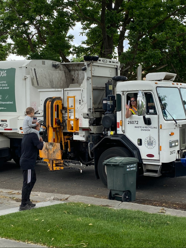 Photograph of a small child on his parent's shoulders waving at a Waste & Recycling crew member who is sitting in the cab of a collection truck about to pick up a green garbage bin.