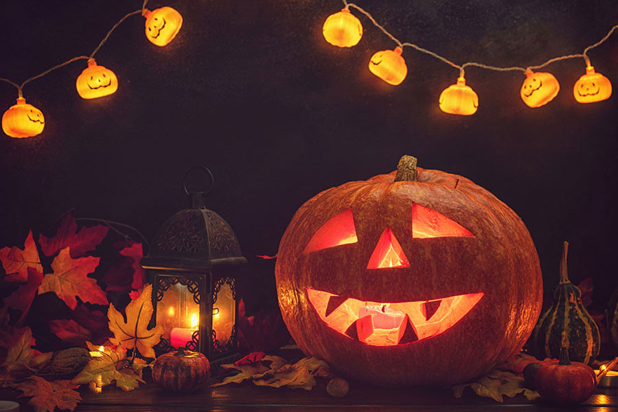 Image of a smiling jack o' lantern in front of a lantern. Leaves are scattered around the pumpkin, and a string of cheerful pumpkin shaped lights frames the top of the image.