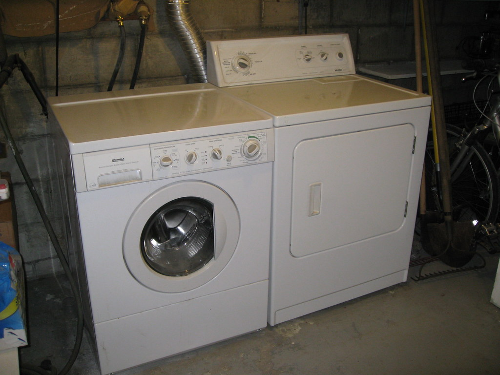 Photo of old washer and dryer in a basement.