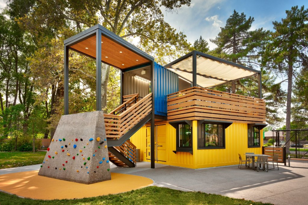 Photo of Tracy Aviary's Bird Feeder Café. The building is constructed out of yellow and blue shipping containers. There is a small rock climbing wall in front for children. Pine and cottonwood trees surround the building.