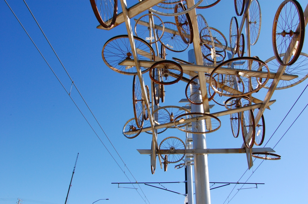Photo of public art at Salt Lake City TRAX station. The Artwork is a steel poll decorated with different sized bike wheels creating a nest of wheels and steel bars juxtaposed with the steel lines of the light rail and the blue sky.