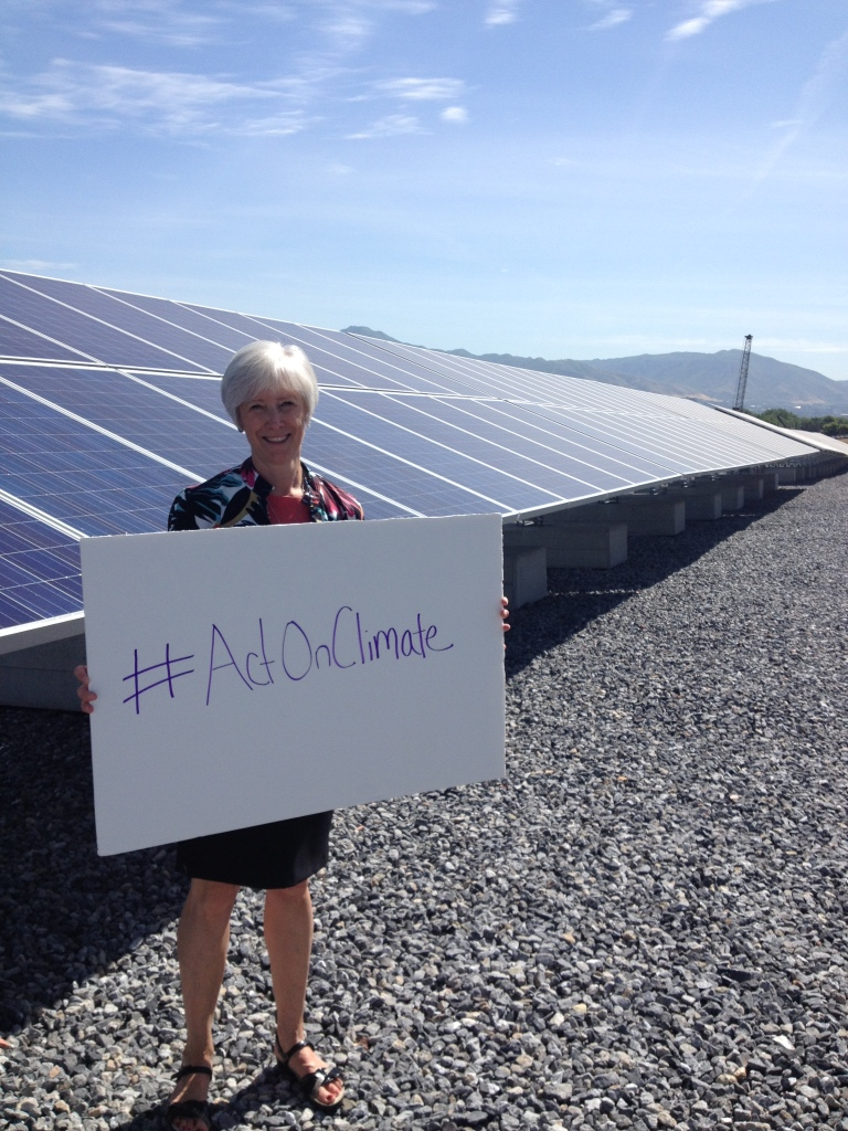 Photo of Vicki Bennett in front of solar panels with a sign reading #ActOnClimate.