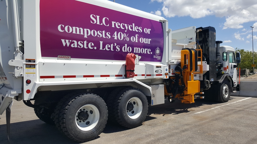 """Photo of SLCgreen Waste & Recycling truck, with a banner that reads """"SLC recycles or compots 40% of our waste. Let's do more."""""""
