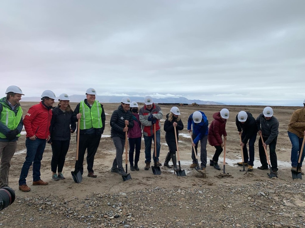 Representatives from Salt Lake City and other organizations stand in a large muddy field with shovels at the Elektron Solar Project groundbreaking event. They are all in colorful windbreakers and white Elektron Solar hardhats.
